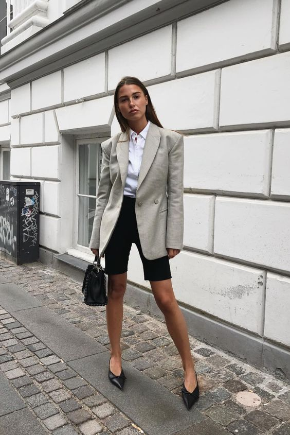 a white button down, black cycling shorts, a grey blazer, black pointed toe shoes and a black bag